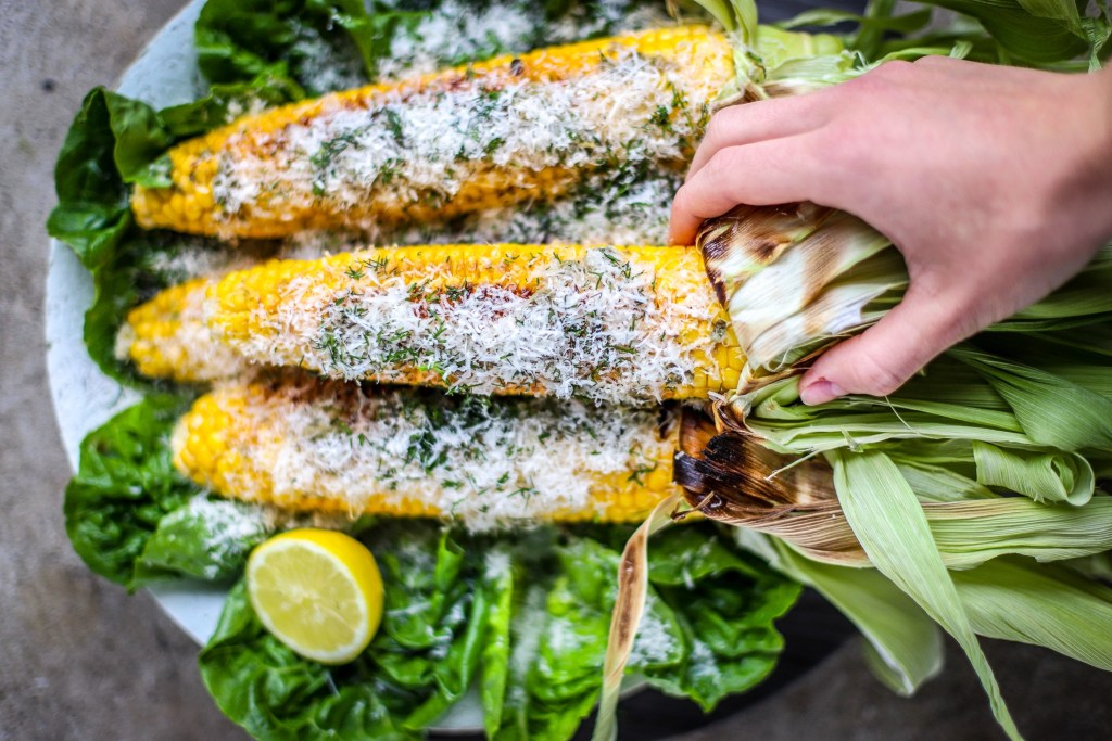 Hand reaching for a buttery grilled sweetcorn from stack.