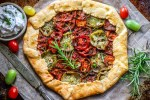 roasted tomato galette with herbs and ricotta dip on dark rust background