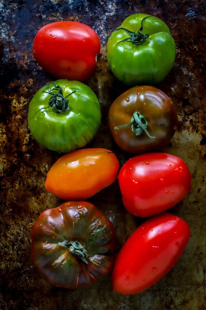 raw heirloom tomatoes nestled together on antique baking tray