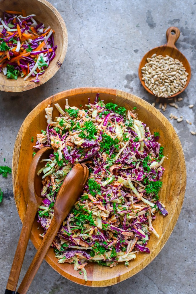 vertical image of creamy sunflower-ranch coleslaw on concrete backdrop