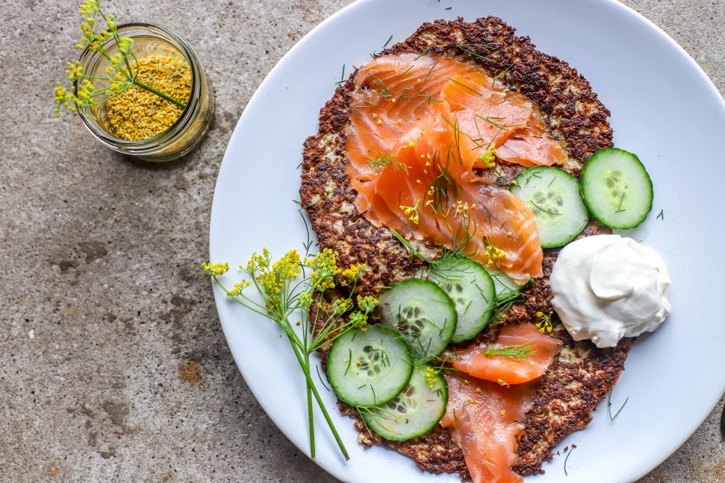 Low-carb cauliflower rostis with smoked salmon, cucumber and sour cream on white plate