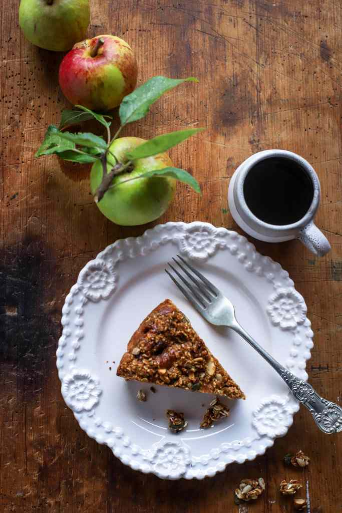 slice of apple streusel cake on white plate, wood background with trio of leafy apples