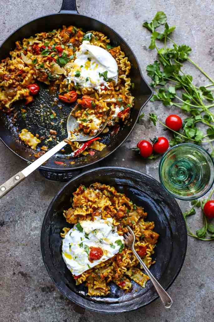 Indian eggplant and tomato pasta in cooking dish and bowl