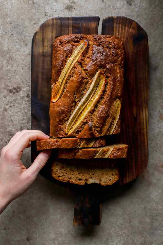vertical image hand reaching for a slice of banana bread on wooden board