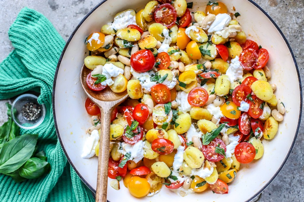 gnocchi tomatoes, cheese in white skillet
