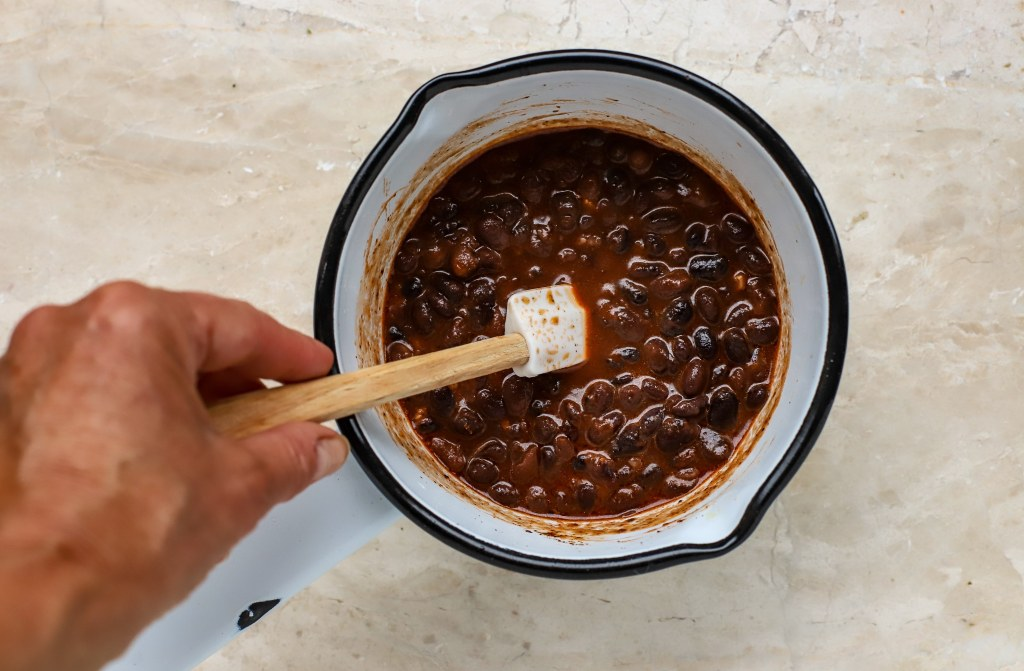 enamel pan with hand stirring beans