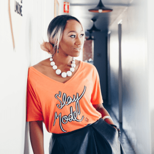 woman leaning against a wall with an orange shirt that reads Slay Mode