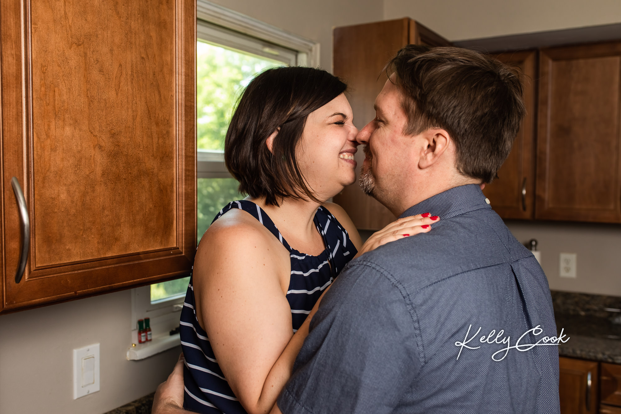 In-home lifestyle engagement photo of an engaged couple cuddling in their kitchen