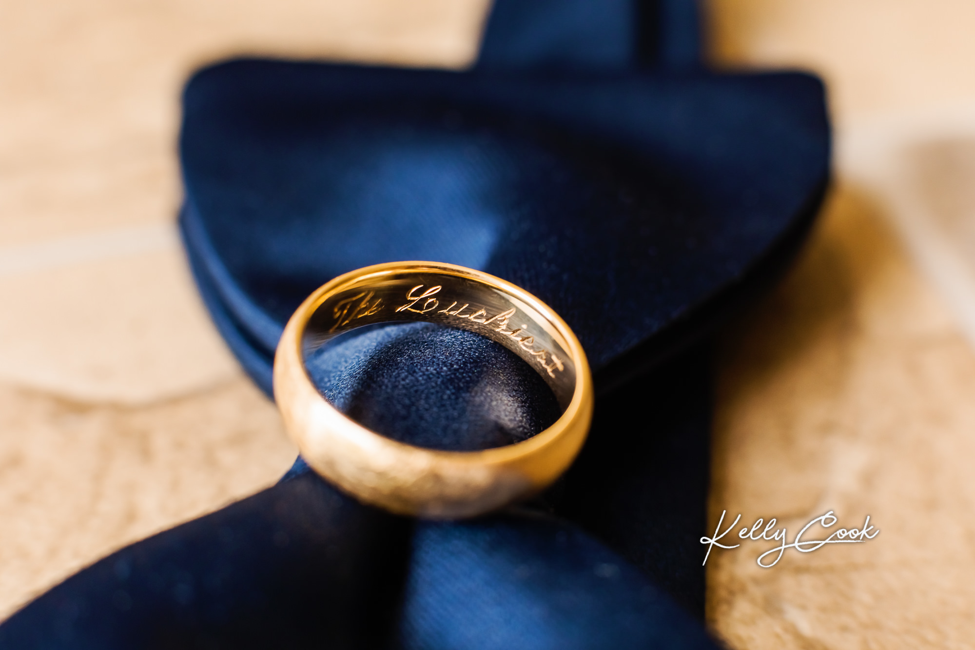 """Close-up photo of the groom's bowite and wedding ring, engraved with """"The Luckiest"""""""