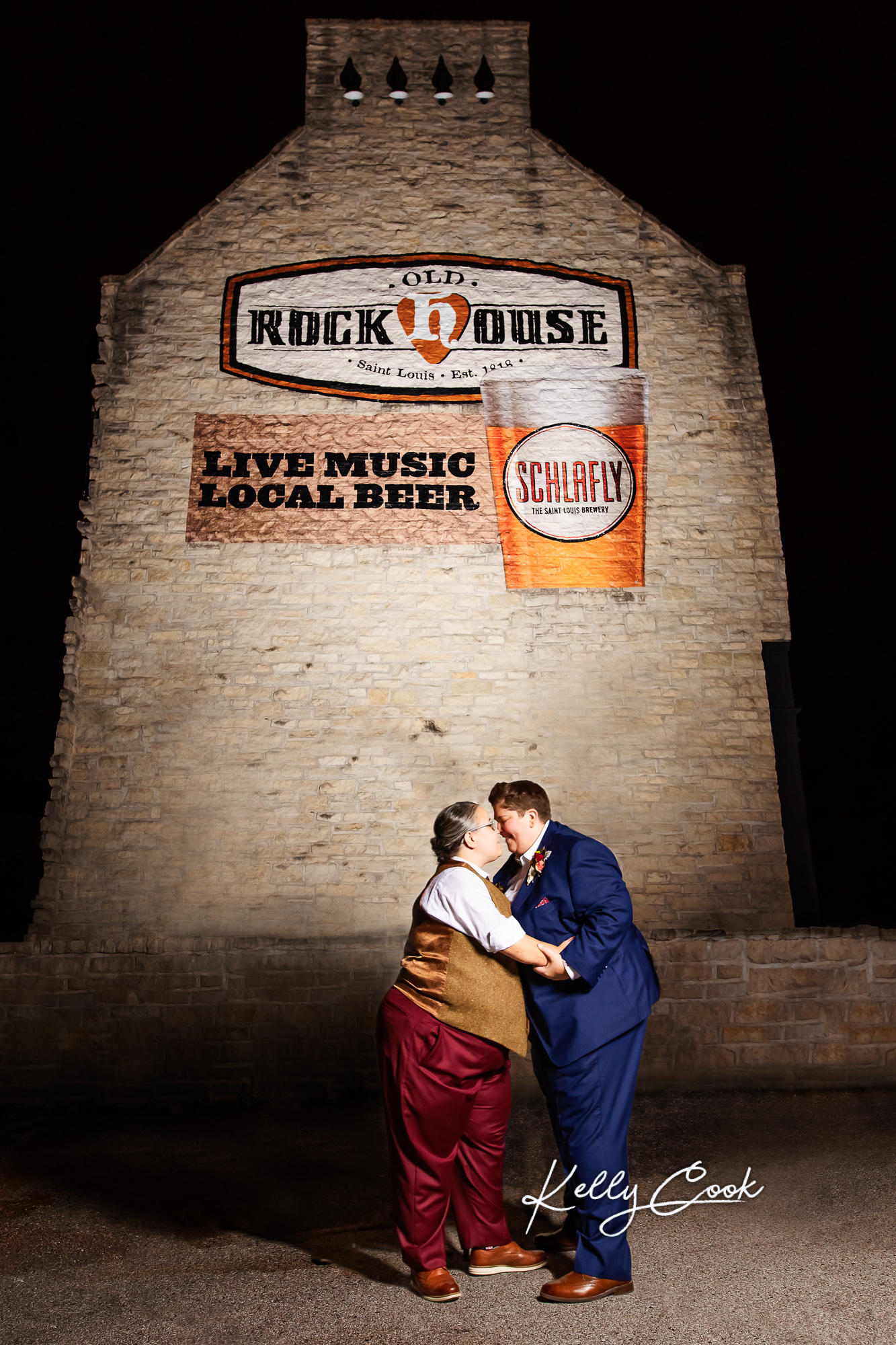 Newlywed couple posing outside of Old Rock House at night