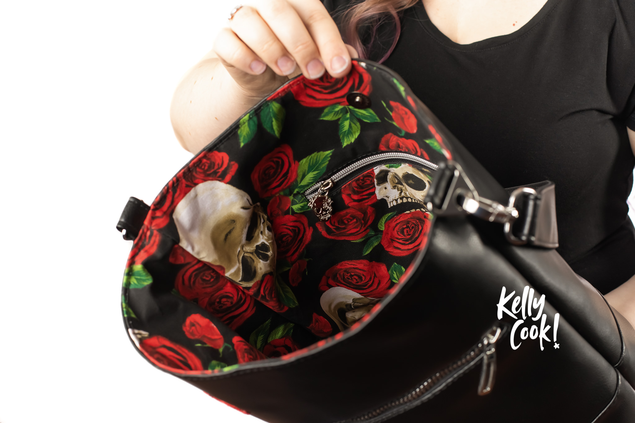 Woman showing off the rose and skull print inside of a purse