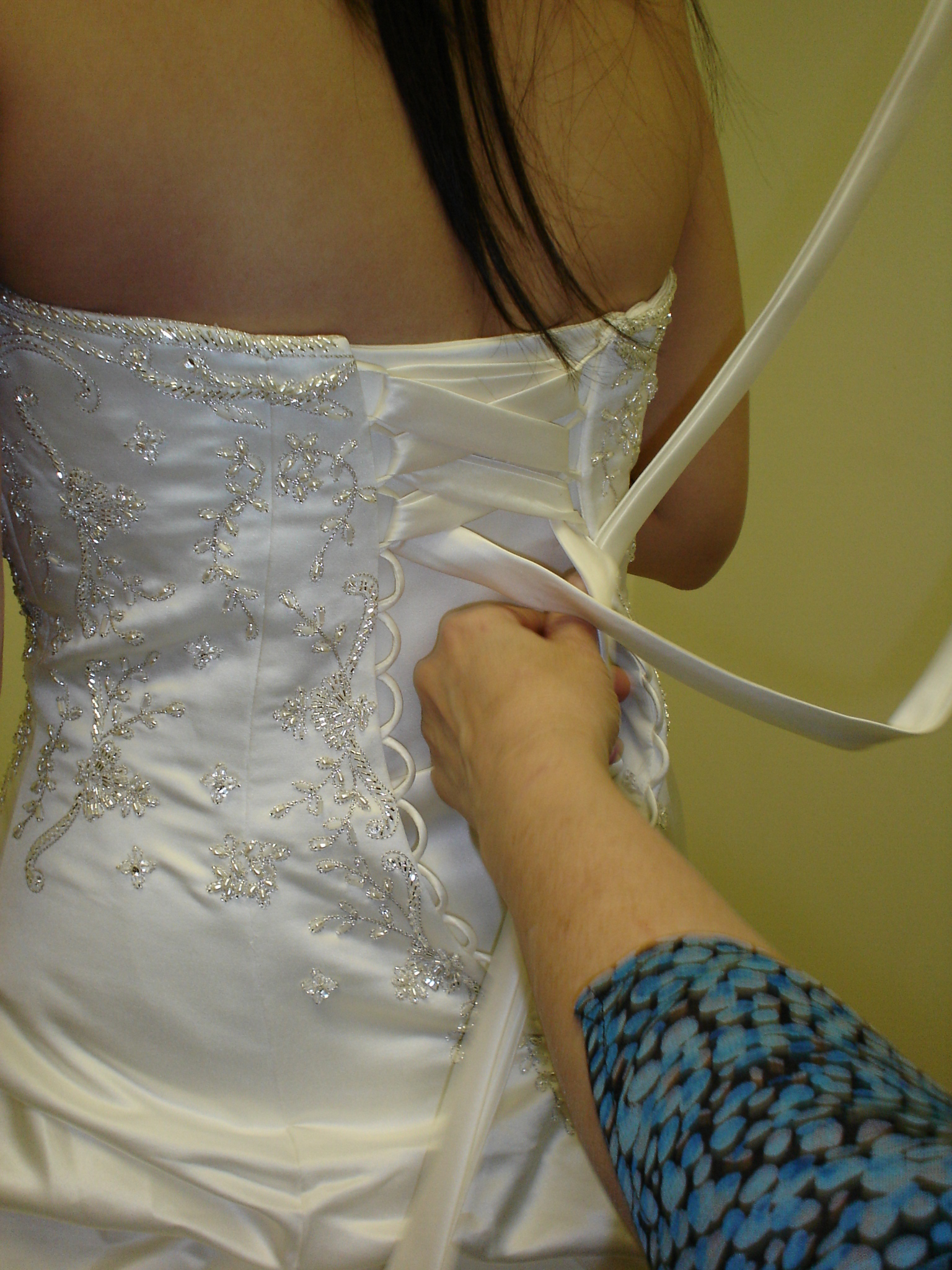The seamstress showing me how to tie the corset.