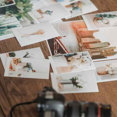 printed photos scattered on wooden table