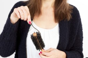 Caucasian woman cleaning her brush from her lost hair
