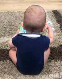 Photo from behind of a 6 month old baby sitting down