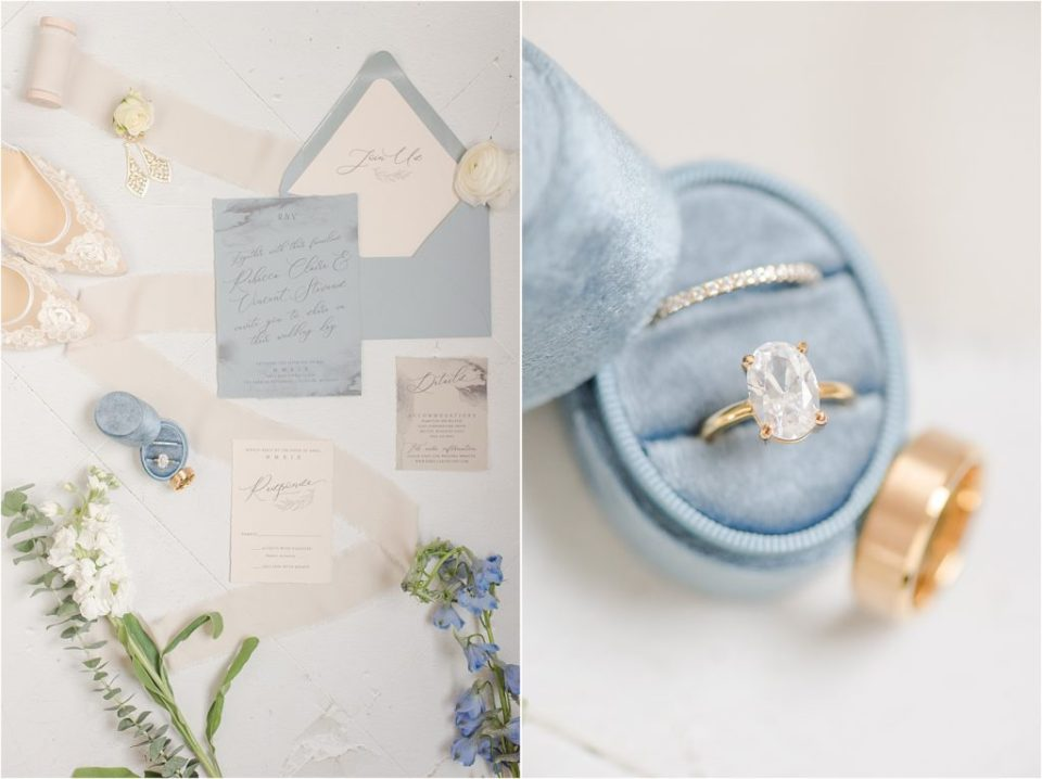 Dusty blue ring box with gold rings and invitation suite