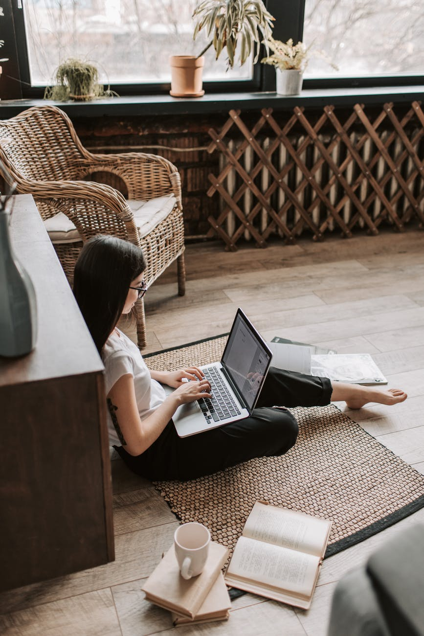 young barefoot woman using laptop on floor near books in stylish living room