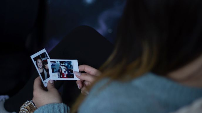 woman holding polaroids of her friends