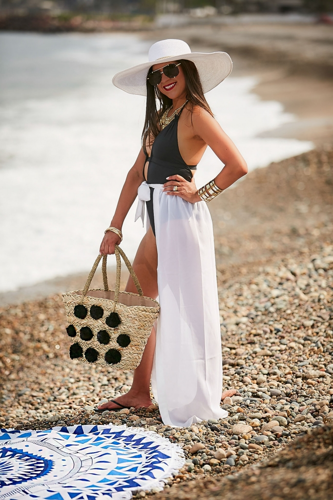 Lifestyle blogger Kelsey Kaplan of Kelsey Kaplan Fashion wearing black one piece swimsuit and pom pom purse