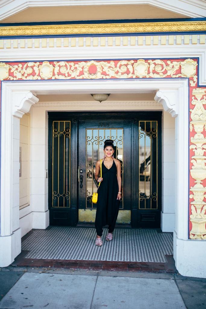 Kelsey Kaplan of Kelsey Kaplan Fashion wearing a black jumpsuit and yellow gucci purse