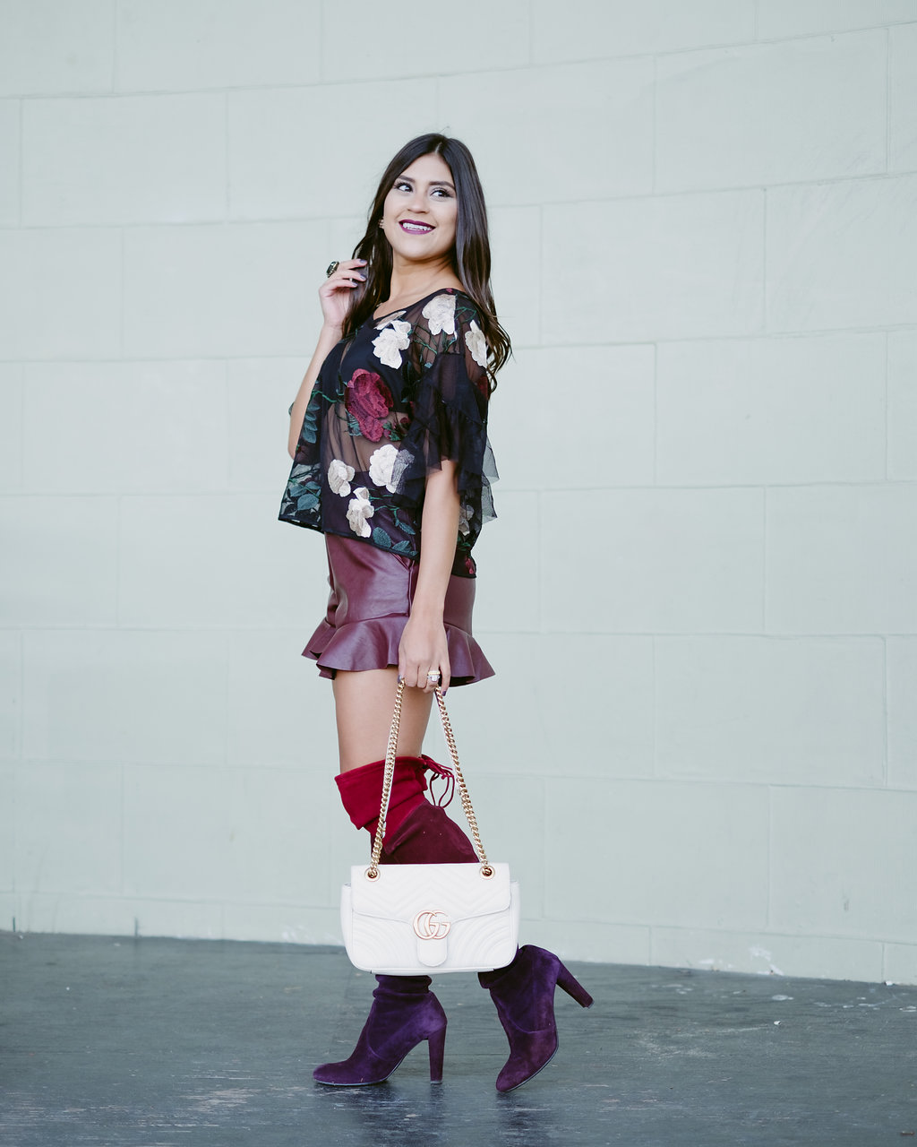 Life style blogger Kelsey Kaplan of Kelsey Kaplan Fashion wearing burgundy faux leather shorts and bordeaux Stuart Weitzman OTK boots