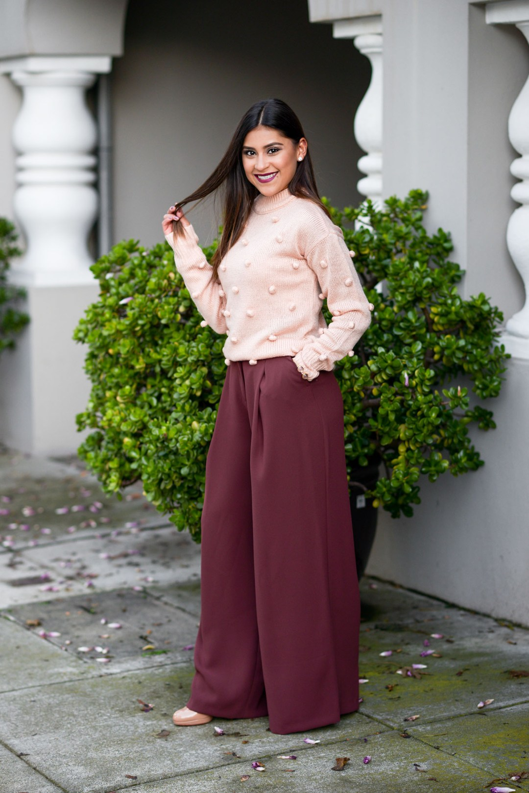 Lifestyle blogger Kelsey Kaplan of Kelsey Kaplan Fashion wearing River Island pants and pom pom sweater for Thanksgiving outfit