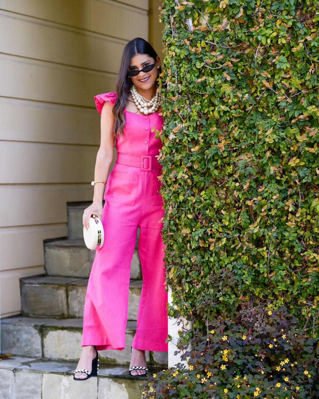 Lifestyle blogger Kelsey Kaplan of Kelsey Kaplan Fashion wearing Pink Belted Jumpsuit and pearl Stuart Weitzman sandals