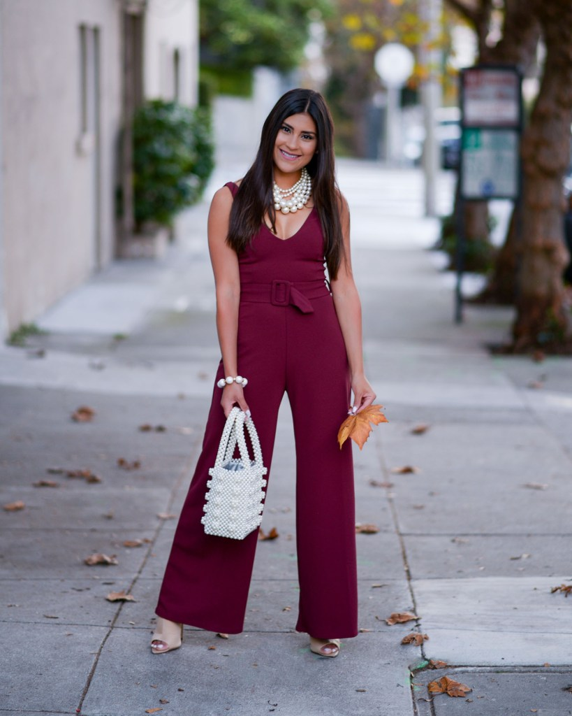 Lifestyle blogger Kelsey Kaplan of Kelsey Kaplan Fashion wearing burgundy jumpsuit and pearl beaded purse