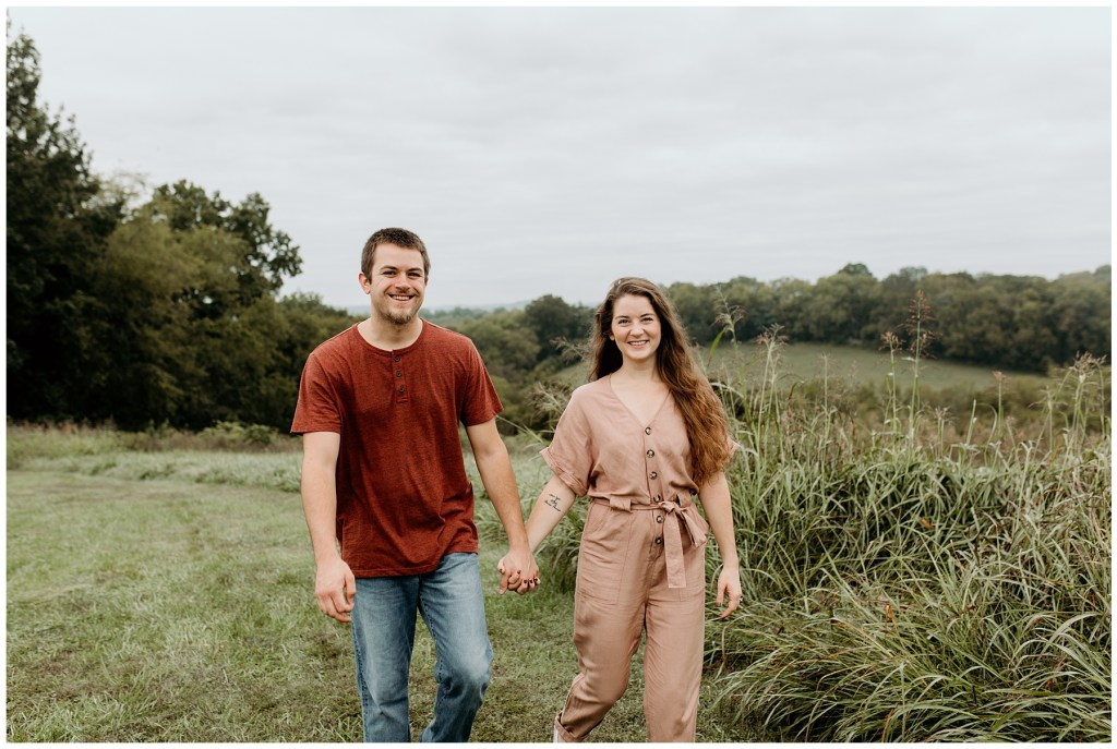 couple walking through tennessee forest during engagement session