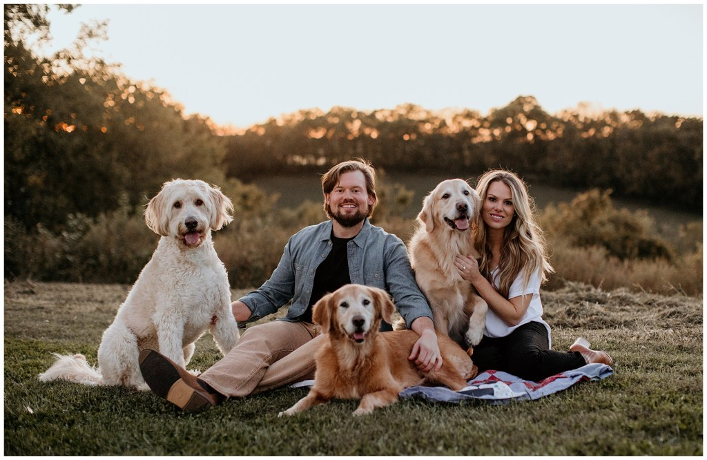 couple posing during engagement session with dogs
