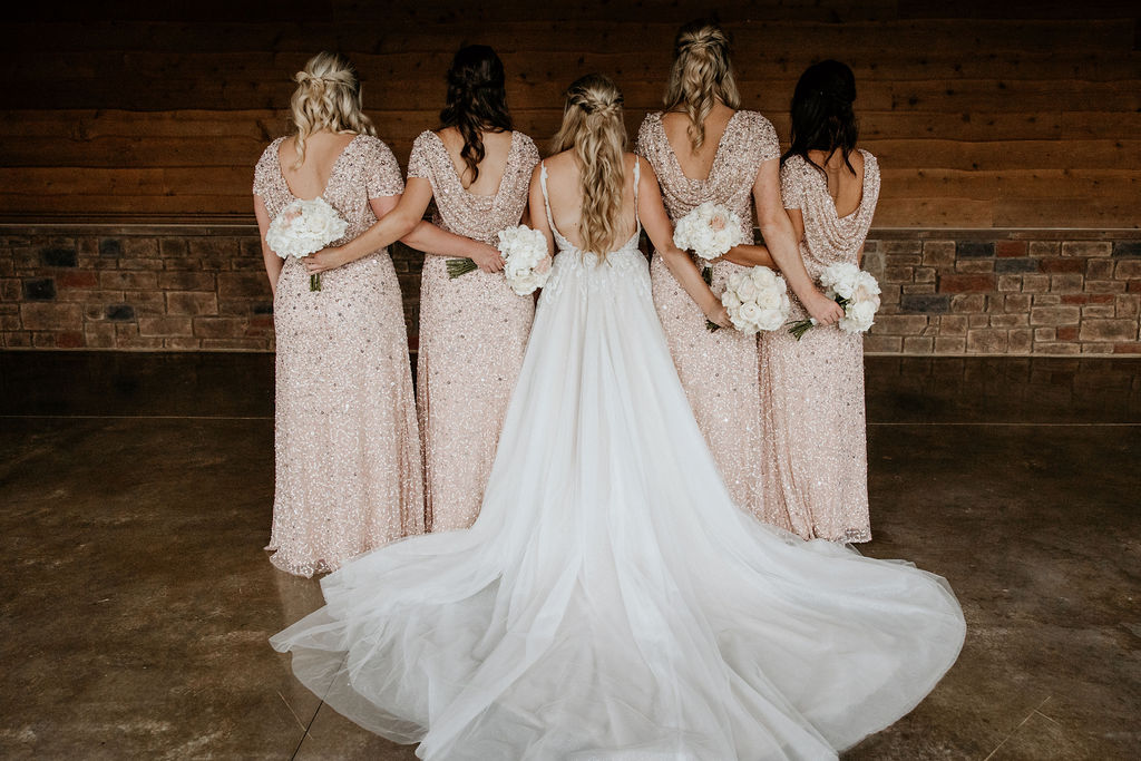 bride posing with bridesmaids at sycamore farms