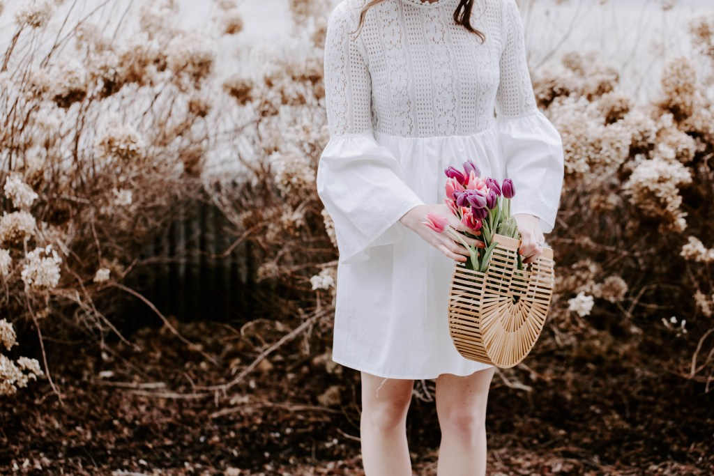 Dress details include flared waist, bell sleeves, and lace high neck. Fresh flowers in pink and purple add a whimsical feel in the bamboo bag