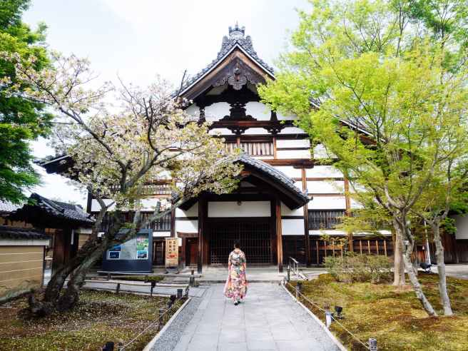 geisha walking towards white building