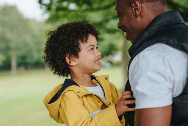 crop cheerful black man interacting with son in city park