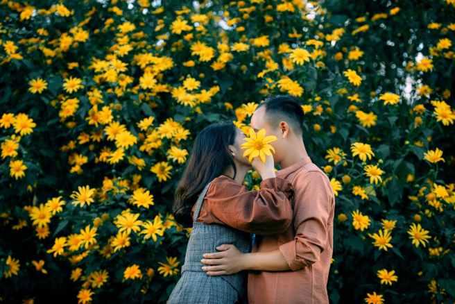 anonymous loving couple hugging near blooming shrub
