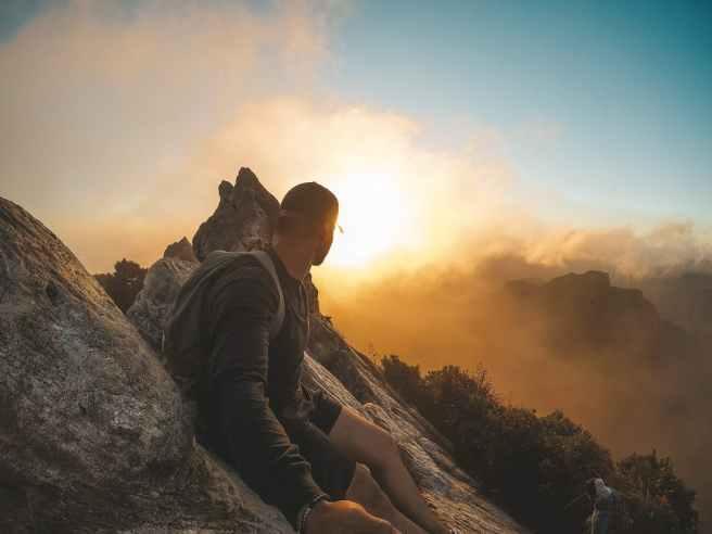 man wearing black long sleeved shirt standing on mountain