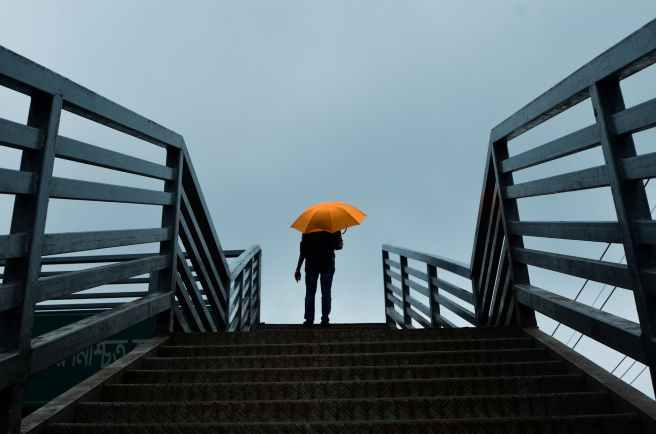 person holding umbrella standing above stairs