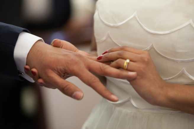 bride putting a ring on grooms hand