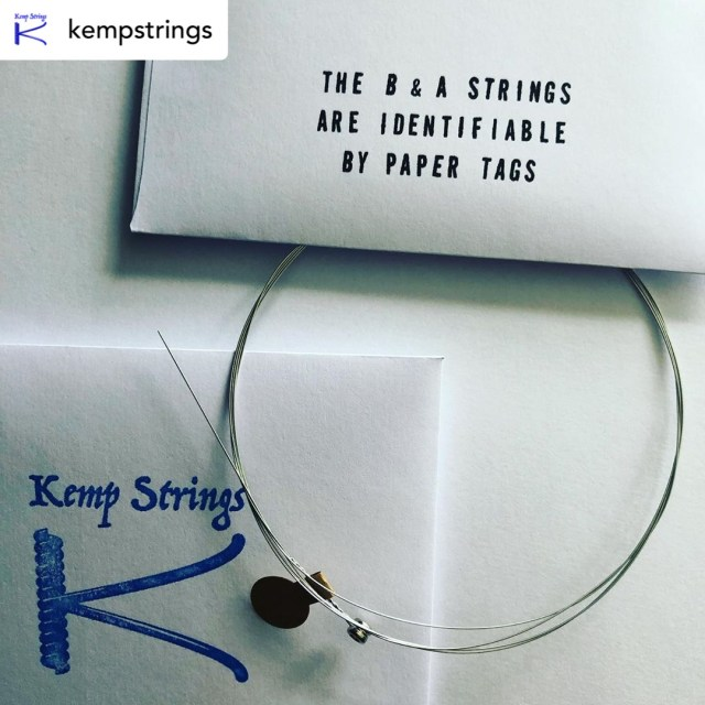 A photograph of Kemp Strings paper envelopes and a guitar string showing how the B and A strings are identifiable by paper tags.