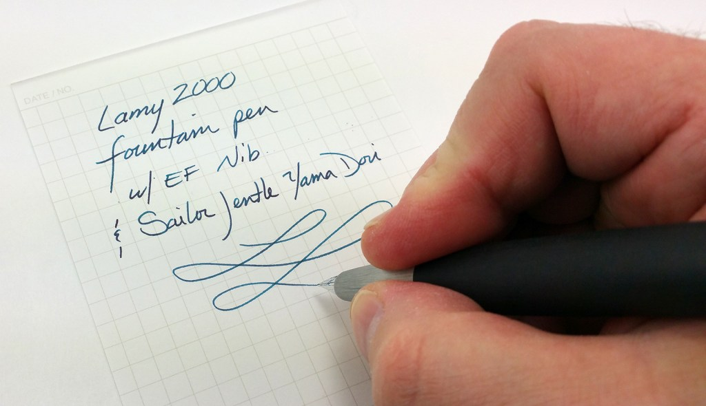 Lamy 2000 Fountain Pen Writing Sample, showing a hand in the process of writing text and a flourish with the pen