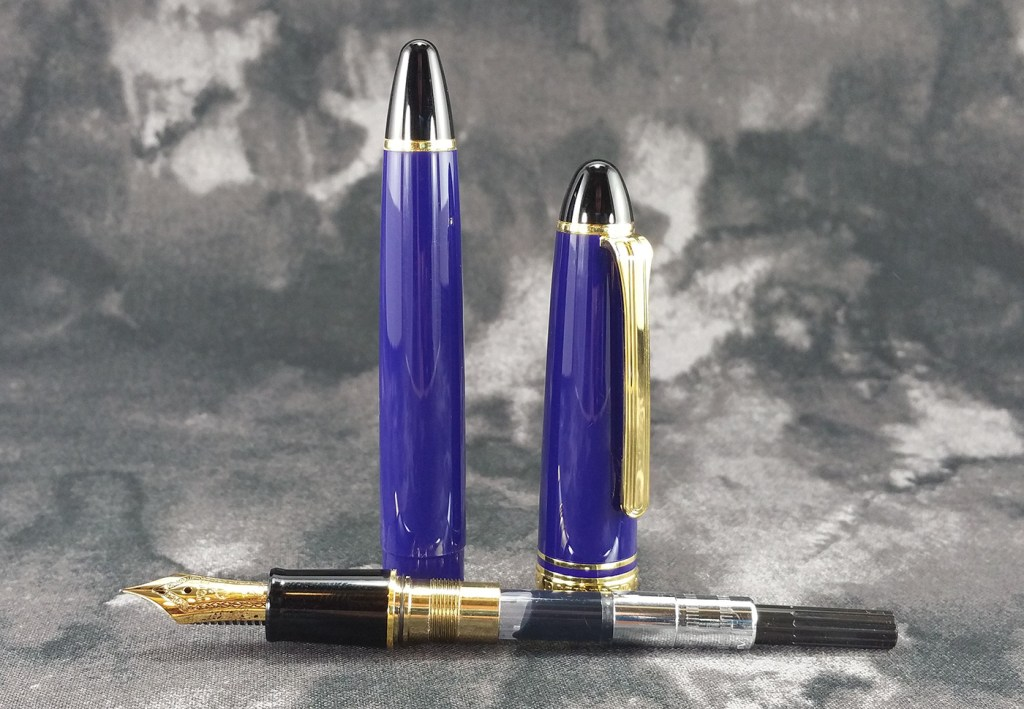 The Sailor 1911 Standard Fountain Pen Disassembled, with the pen's internals laying down horizontally while the barrel and cap stand up behind
