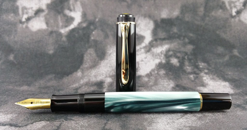 The Pelikan Classic M200 Fountain Pen laying down, uncapped, with the cap standing up behind the pen