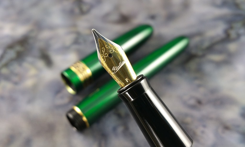 Close-up shot of the Italix Parson's Essential Fountain Pen Nib and Section, with the barrel and cap in the background