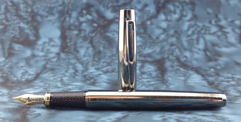 The Yiren 856 Fountain Pen, uncapped, with the pen laying down and the cap standing up behind it
