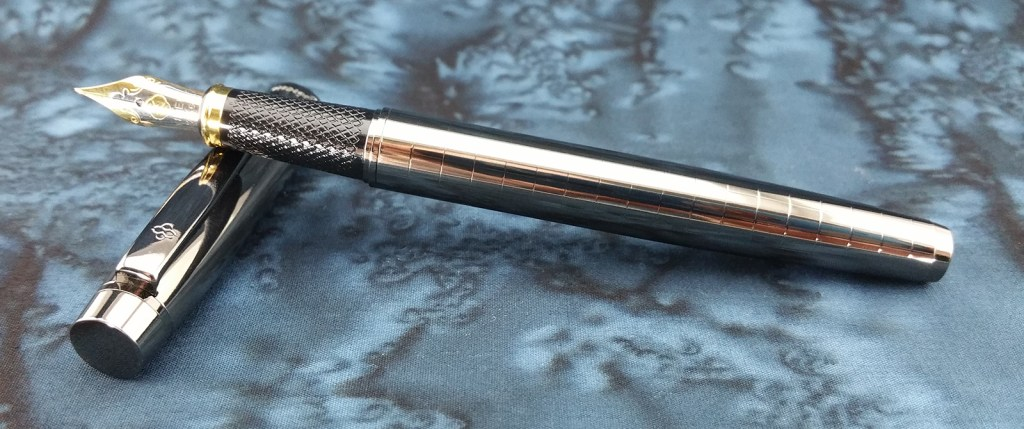 The Yiren 856 Fountain Pen, uncapped, with the cap laying down and the pen laying on top of it
