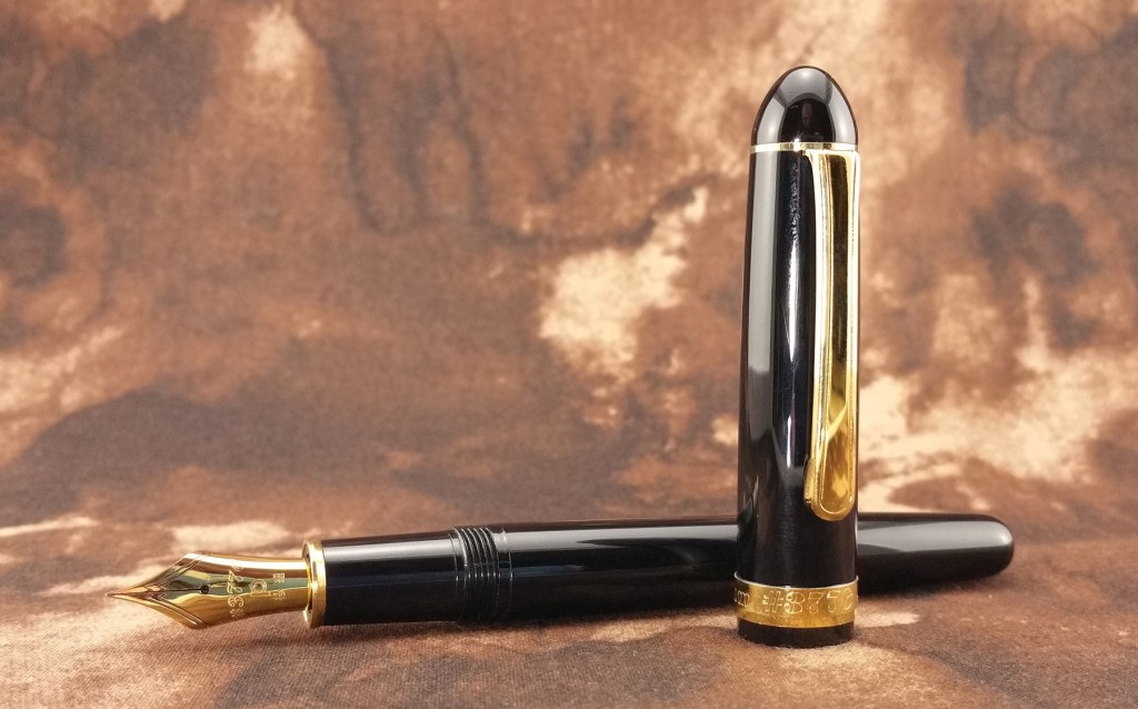 The Platinum 3776 Balance Maestro Fountain Pen laying down, with the cap standing up in front of it
