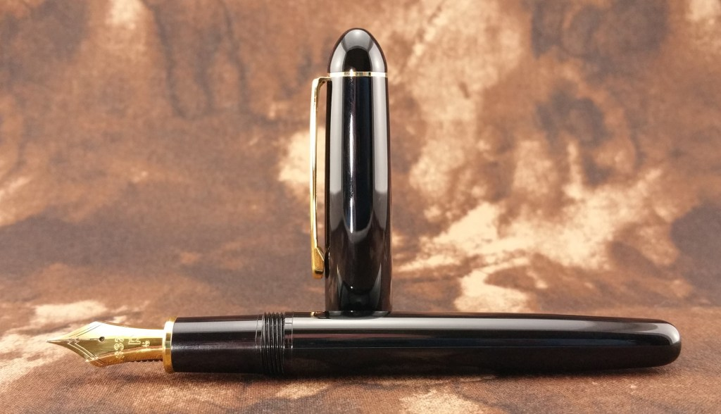 The Platinum 3776 Balance Maestro Fountain Pen laying down, with the cap standing up behind it