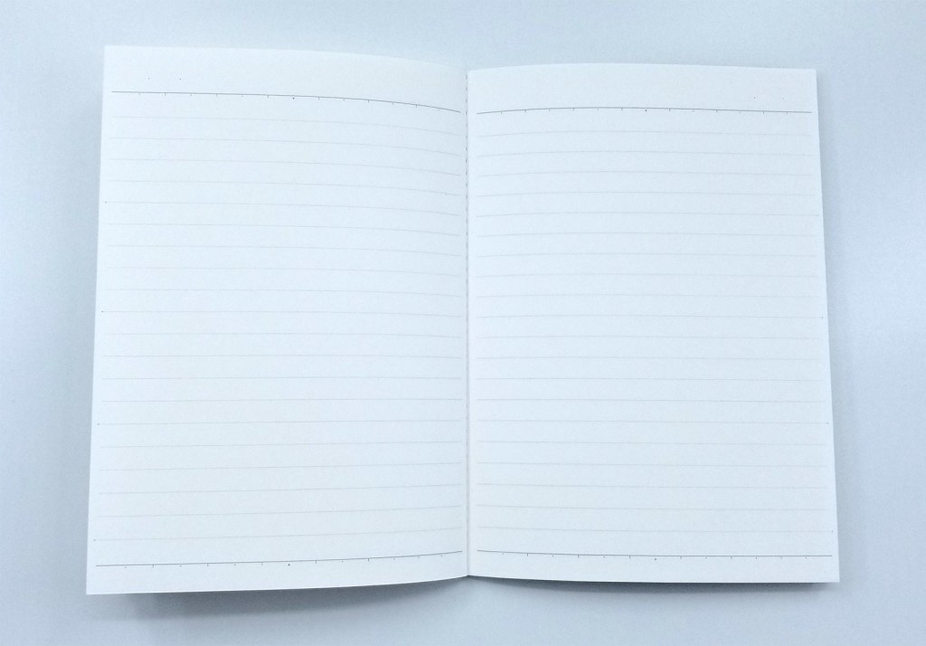 A photo of the Kokuyo Systemic A6 Notebook Refill, lying open, showing the 6mm light gray ruling and the special spacer ruling at the top and bottom of each page