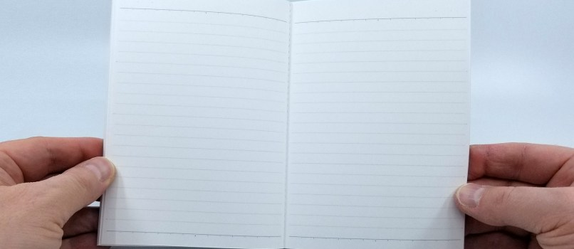 A photo showing the Kokuyo Systemic A6 Notebook Refill being held open, showing the 6mm light gray ruling and the special spacer ruling at the top and bottom of each page