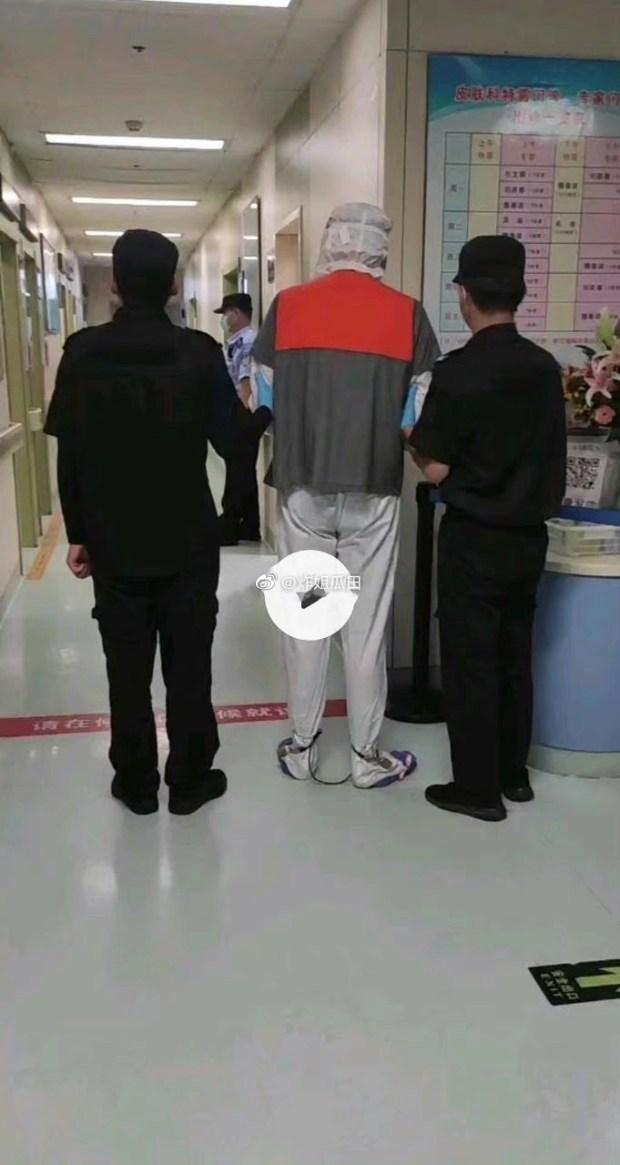 Rầm rộ hình ảnh Ngô Diệc Phàm trong bệnh viện: Bị trùm kín đầu, xích 2 chân, cảnh sát kèm chặt 2 bên - Ảnh 2.